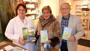 Apothekerin Erika Stehr präsentiert ihren Kalender, Kundin Ilse Pietsch hat sich von Autor Peter Jäger sein Engel-Buch signieren lassen
